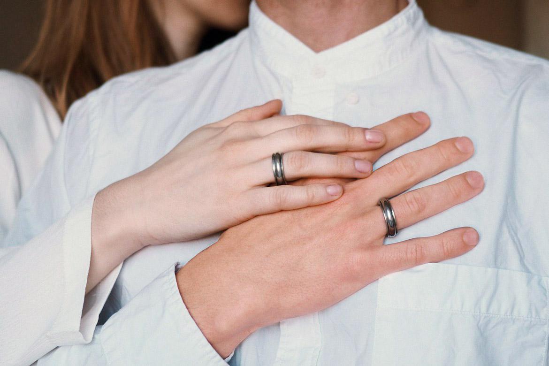 мужская и женская рука с оловянными кольцами