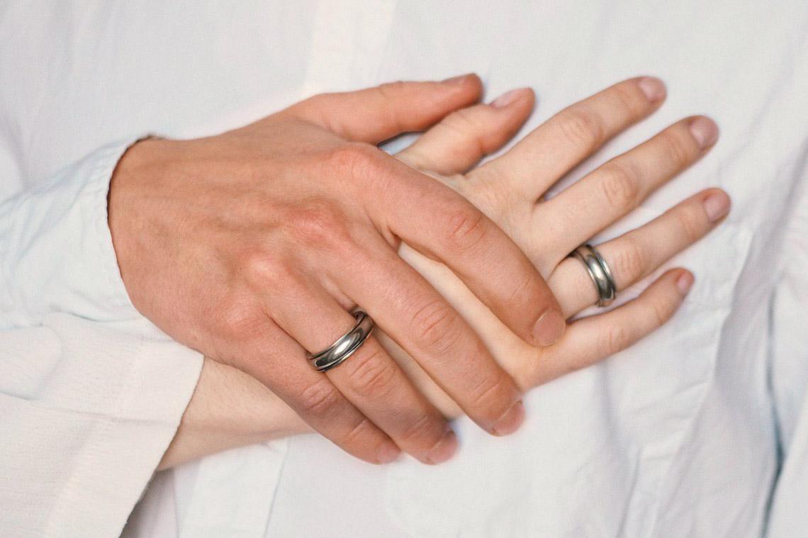 крупный план мужской и женской руки с оловянными кольцами