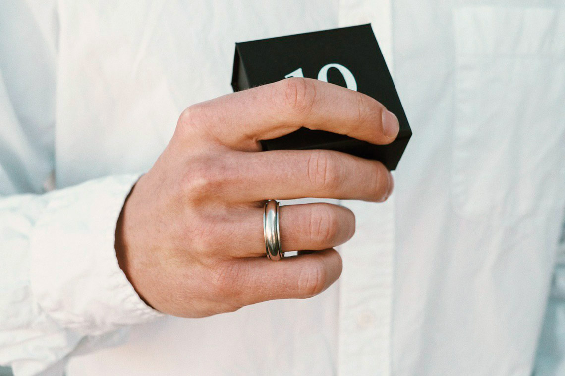 мужская рука держит подарочную коробку с оловянным кольцом