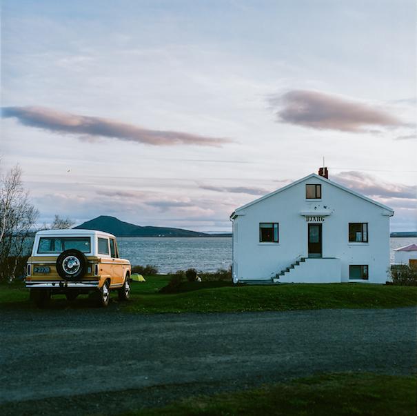 старый джип у белого дома на берегу в Исландии