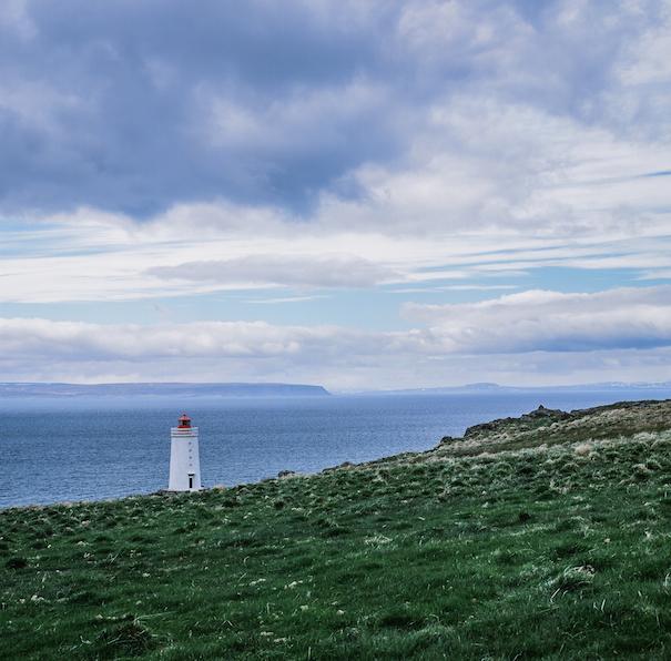 белый маяк на горизонте в Исландии